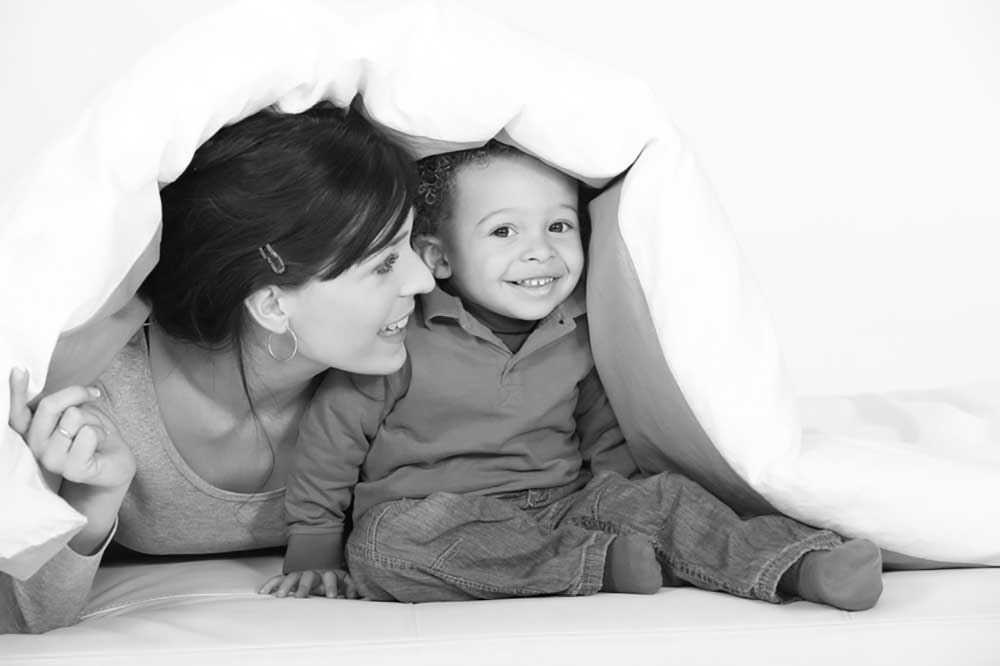Image of a woman playing with a baby under a white coverlet depicting the idea of adoption.