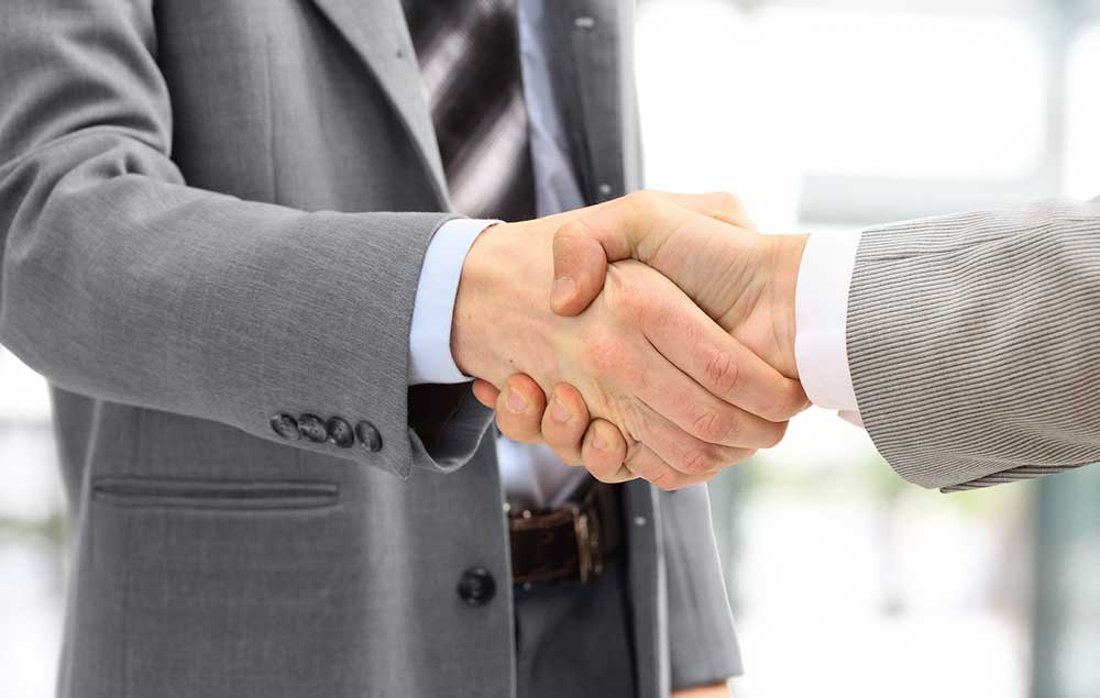 Image of two men shaking hands in agreement.