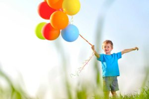 Picture of a small boy in a field of grass holding a cluster of brightly colored helium balloons on a string