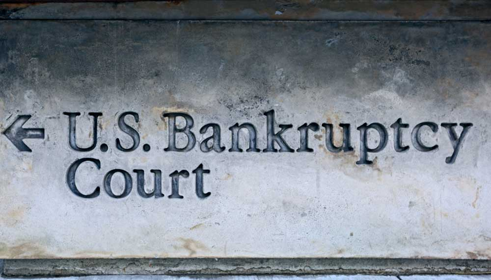 Directional image of the words U.S. Bankruptcy Court engraved into the side of a building showing the way to the bankruptcy court.