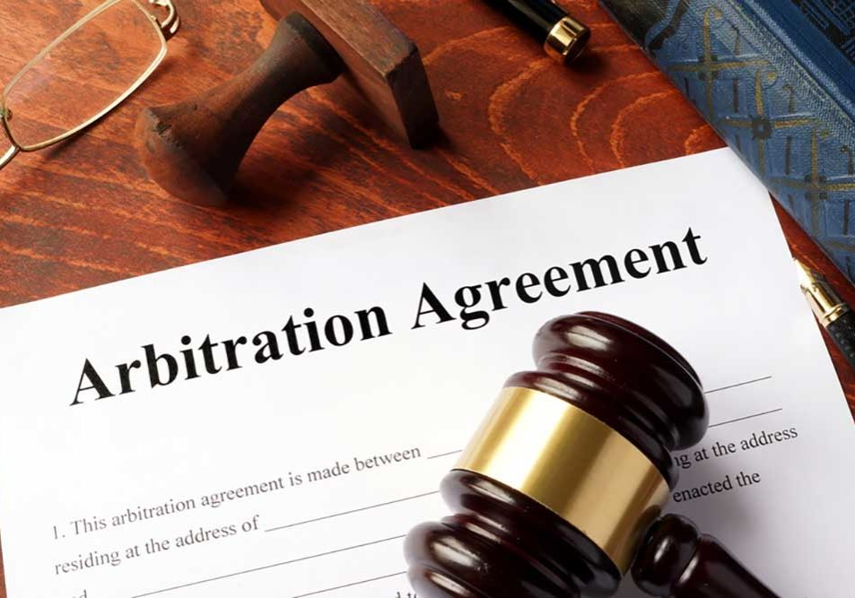 Image of an incomplete arbitration agreement on a wooden desk with lawyerly things, a pen, a stamp, reading glasses, a law book and a gavel.