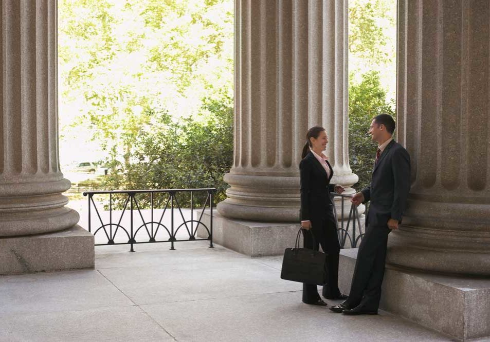 Image of two lawyers in an outdoor rotunda of a courthouse, smiling collegiately to one another during a discussion depicting the concept of attorney camaraderie.