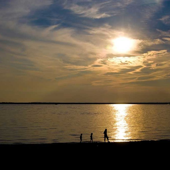 Single parent and two small children walking on the distant beach at dusk in silhouette.