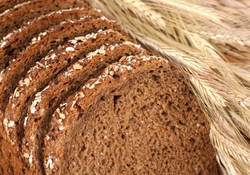 """Image of sliced brown bread with stalks of wheat referencing the idea of a """"breadwinner""""."""