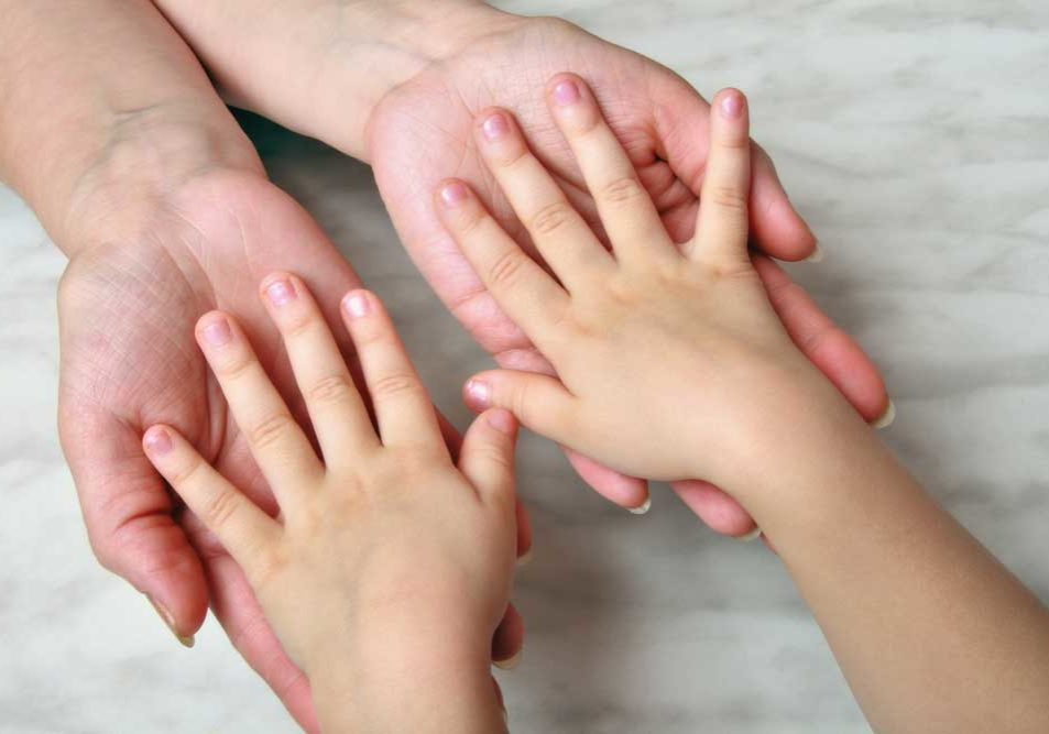 Image of small child with hands, palms face down, in the hands of an adult, depicting child support