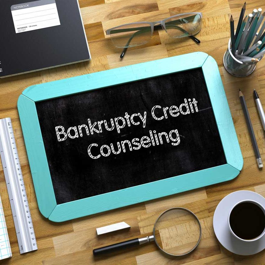 Staged image of a desk top featuring a tablet with the words Bankruptcy Credit Counseling on it.