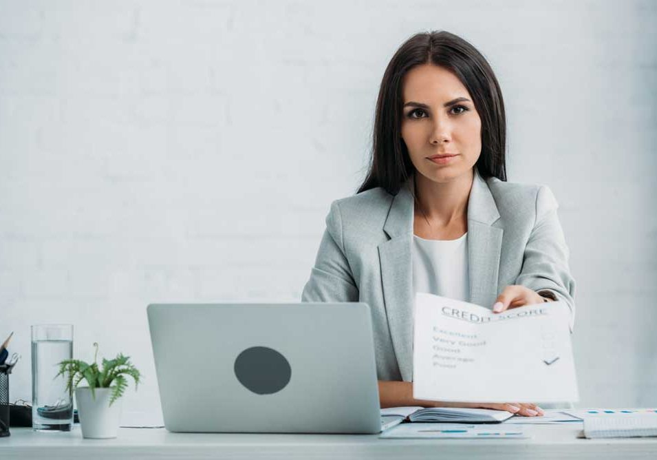 Image of woman sitting behind a desk with a laptop between her and the foreground, holding out a credit report document to an unseen recipient.