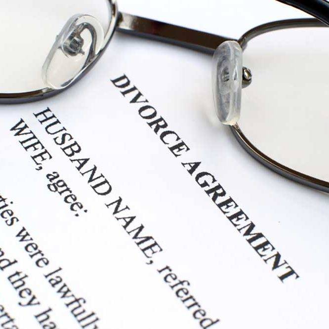 Image of a typewritten agreement for divorce on white paper with a pair of eyeglasses folded on top of it.