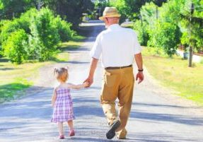 Photograph of a grandfather and preschool granddaughter walking away on a wide path through a path