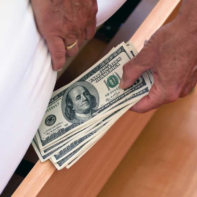Picture of a man's hands wearing a wedding ring hiding money under the mattress.