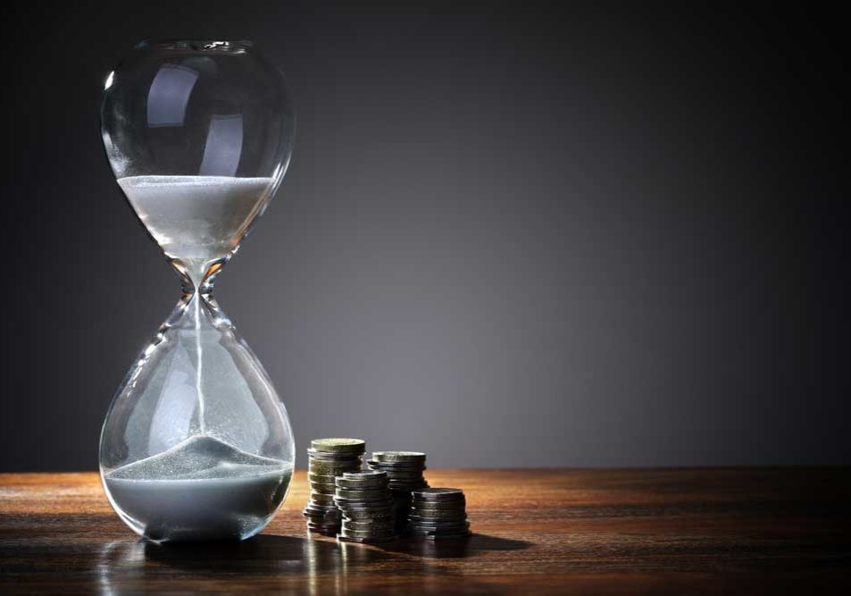 Image of an elegant hourglass on a wooden table in front of a gray wall, representing time and money.