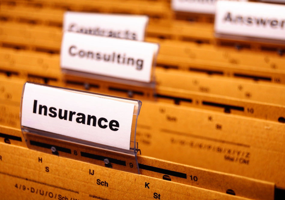 "Image taken from across the top of a filing cabinet drawer with hanging file folders with plastic tab separators. The foremost forward tab is labeled ""Insurance"" while remaining tabs are slightly out of focus."