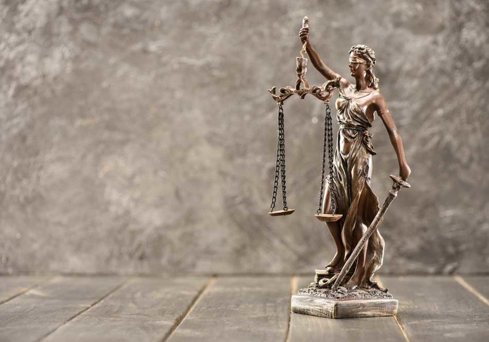 Small statue of Lady Justice against marble.
