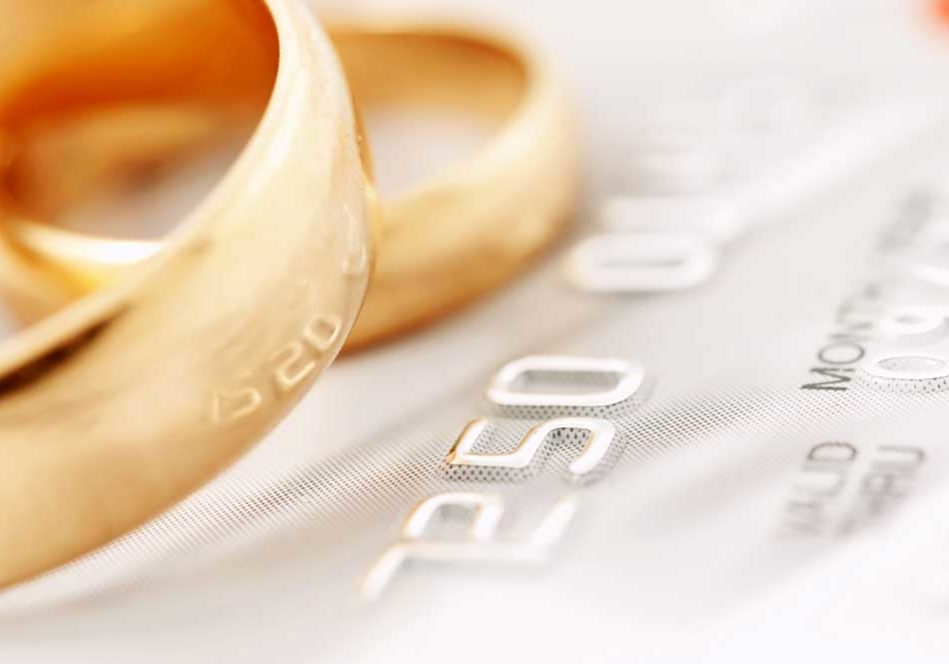 Closeup image of a credit card with wedding rings on the top of it depicting marital debt.