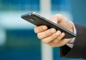 Image of a man's hand using a mobile phone in a corporate atmosphere.