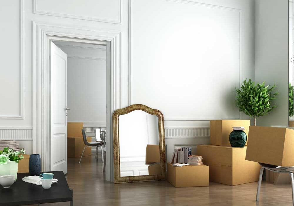 Image of empty room with high ceilings and shiny wood floors with seeral boxes packed and ready to go depicting relocating.