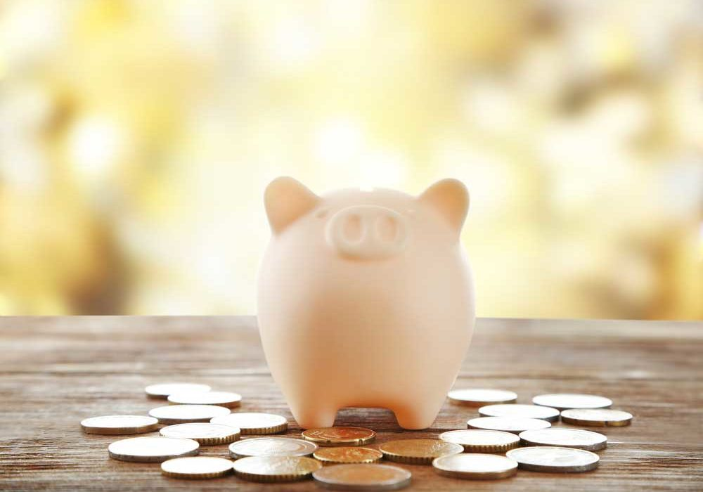 Image of a ceramic pig bank with change spread across a wooden table denoting costs of a divorce.