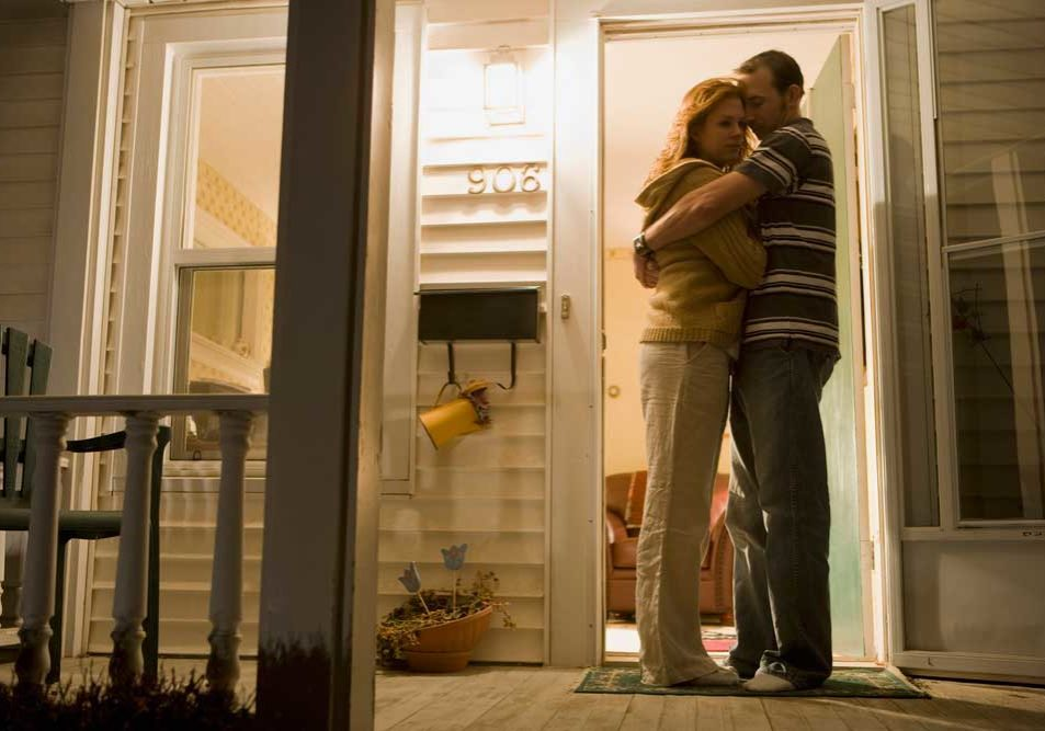 Couple embracing on a front porch depicting reconciliation during divorce.