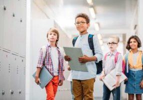 Image depicting children in a brightly lit school corridor.