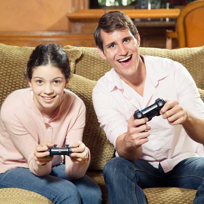 Siblings of significantly different ages playing video games together and smiling
