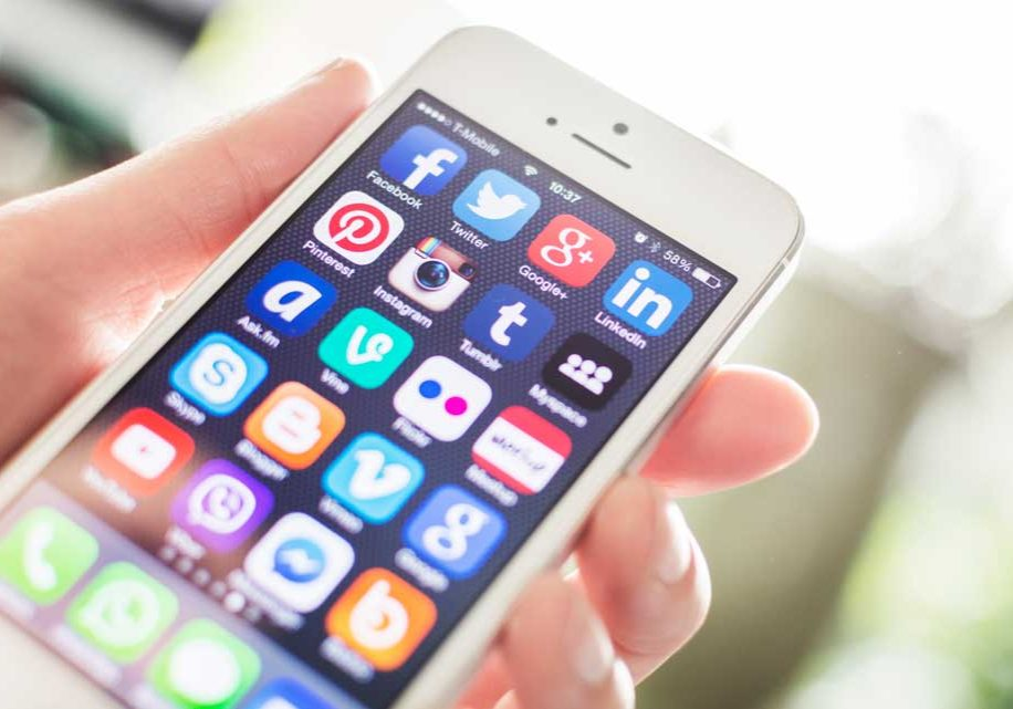 Image of lady holding mobile device covered with social media app icons