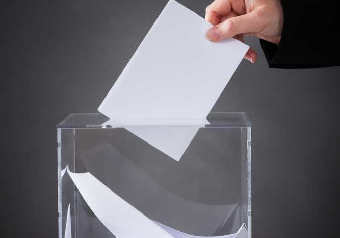 Image of a person dropping a card into a clear glass container, like a suggestion box or ballot bowl.