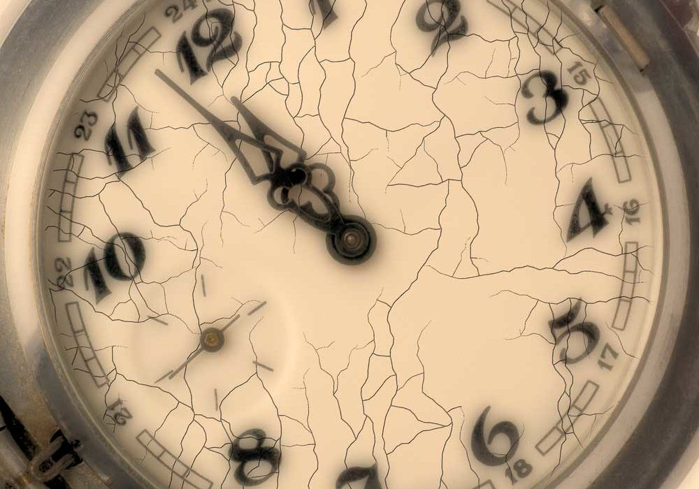 Cracked face of a traditional timepiece depicting the slow movement of time.
