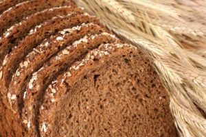 "Image of sliced brown bread with stalks of wheat referencing the idea of a ""breadwinner""."
