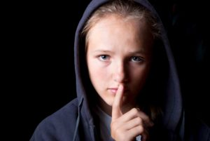 Image of a child wearing a black hoodie on a black background with his finger in front of his lips illustrating saying nothing.