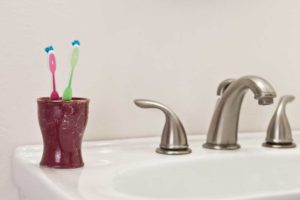 Image of two toothbrushes on a bathroom sink depicting living together