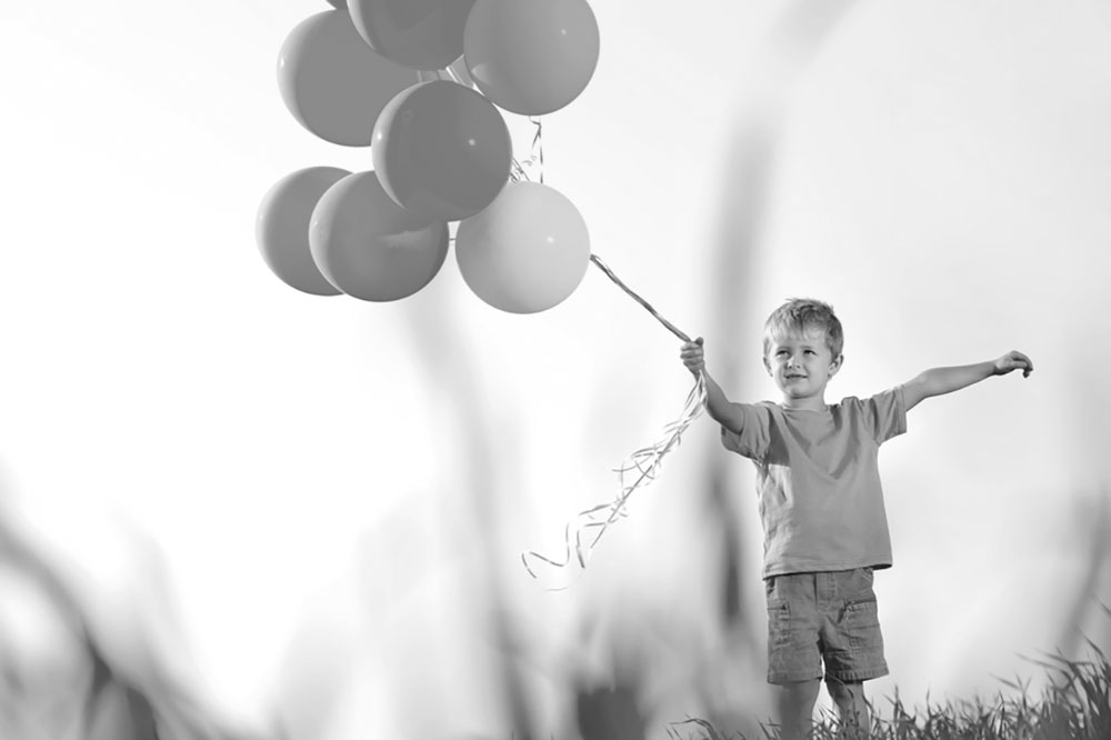 Black and white stock photograph of a small boy holding wind-blown balloons on a field denoting a healthy, happy child.