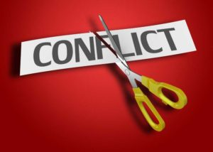 Image of the word CONFLICT on a red background being cut by a scissor.