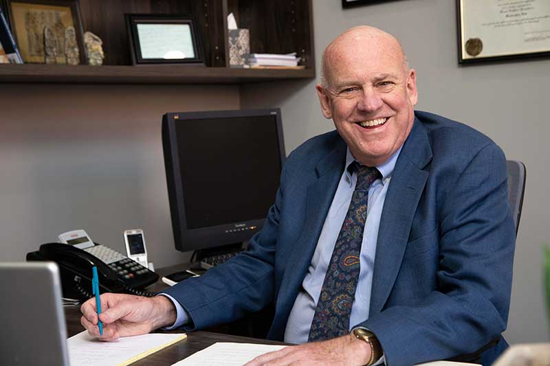 Image of David R. Hillier smiling at the camera from behind his desk.