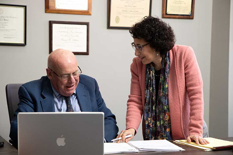 Image of David R. Hillier and his paralegal Idelle Davids discussing documents.