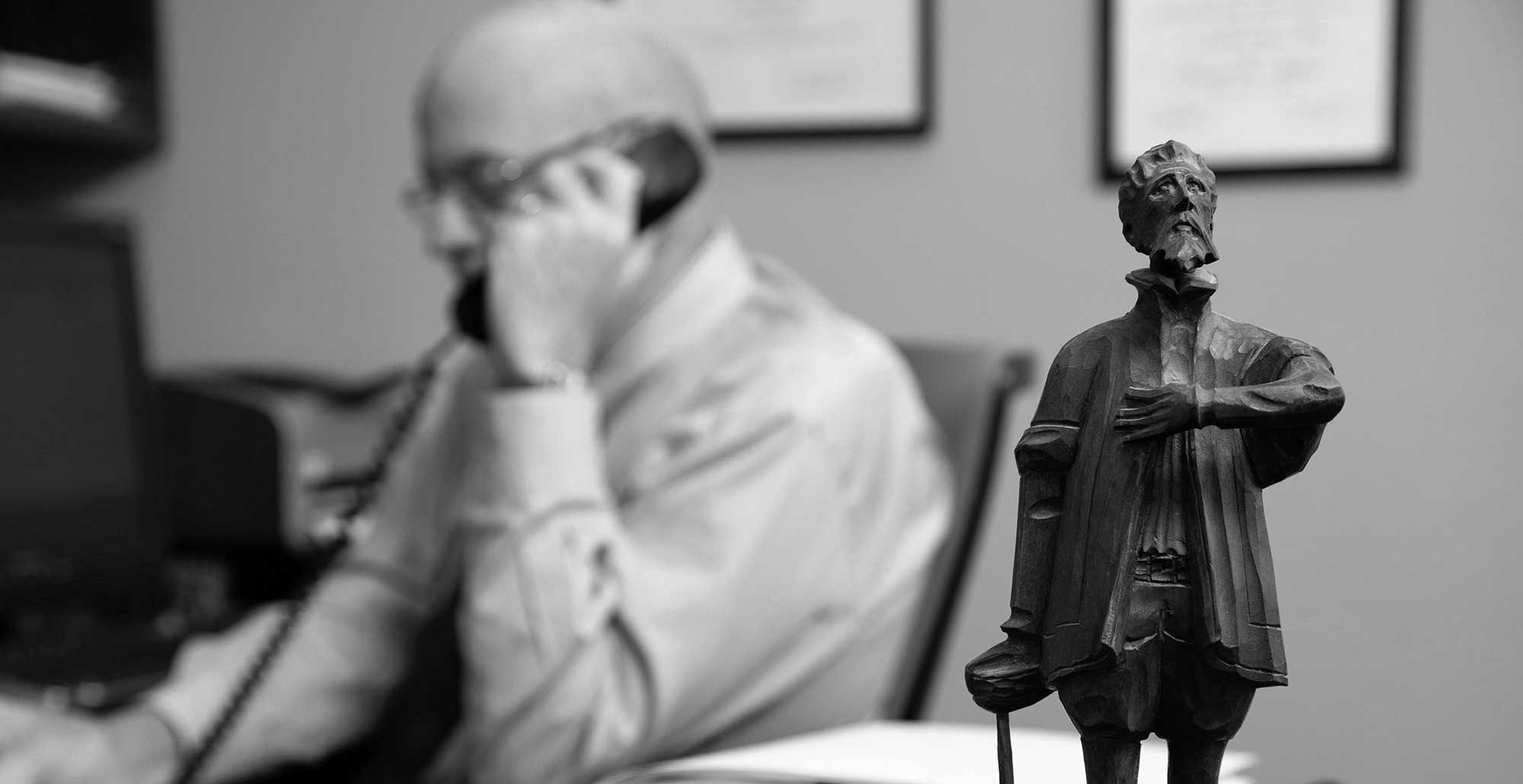 Dave Hillier in his office on the phone with statue in foreground