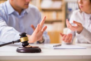 Image of two people sitting at a desk cropped so that faces are implied. The gavel in the foreground denotes a legal proceeding and the hand gestures of the subjects implies that one spouse disagrees.