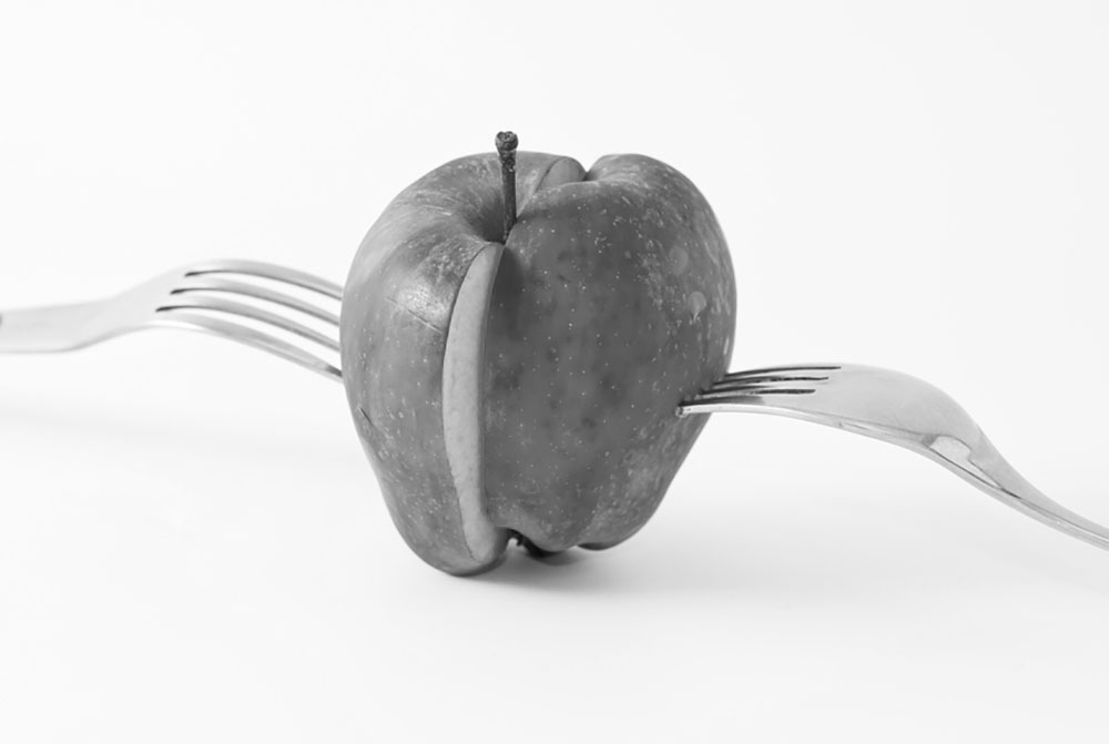 Black and white image of an apple sliced in half with forks protruding from each of the halves denoting equal distribution and splitting of marital property