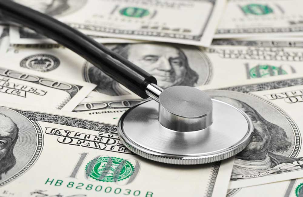 A pile of money with a stethoscope depicting monitoring of financial health.