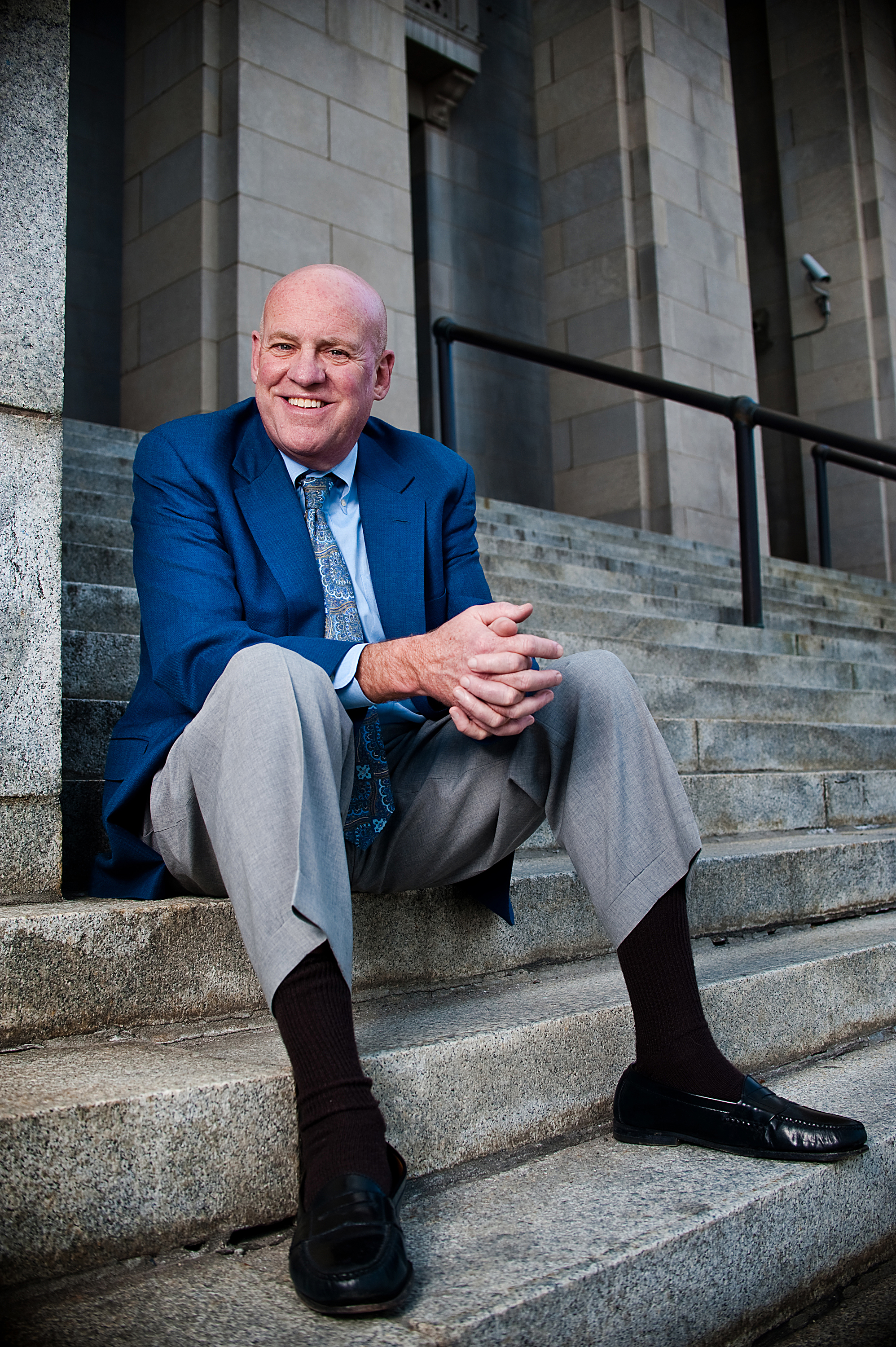 Dave Hillier sitting on the granite stairs in front of the Federal Courthouse in Downtown Asheville (United States District Court for the Western District of North Carolina, where Bankruptcy Court is housed)