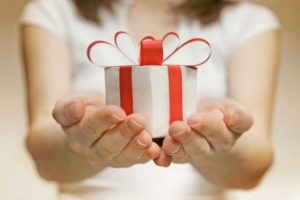 Image of a woman with her hands held together in front of her holding a small white package with a red bow.