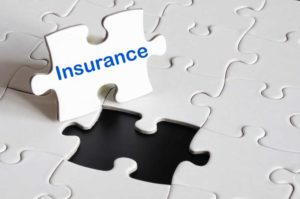 A white puzzle with one missing piece labeled insurance suggesting that insurance is a part of the puzzle