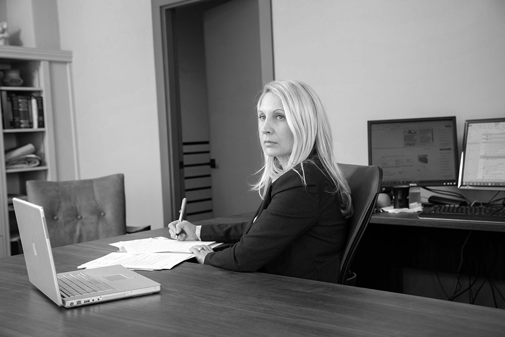 Black and white image of Janet Amburgey in her office in downtown Asheville.