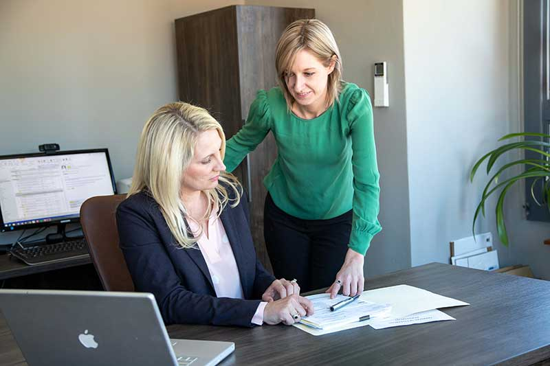 Image of Janet Amburgy and her paralegal Tracy Laws discussing documents.