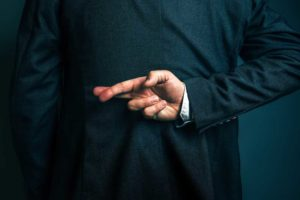 Image of the back of a man in a suit with his right arm bent behind his back and his fingers crossed, depicting the act of a lie.
