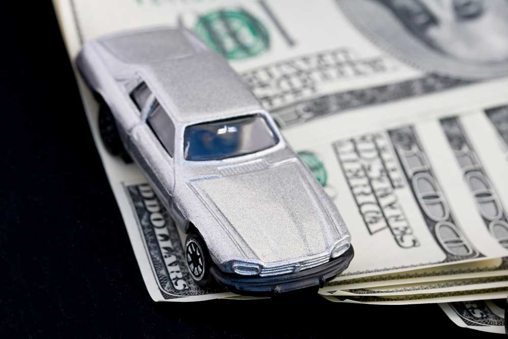 Image of matchbox car sitting on top of cash representing cash loans from family or other private agreement