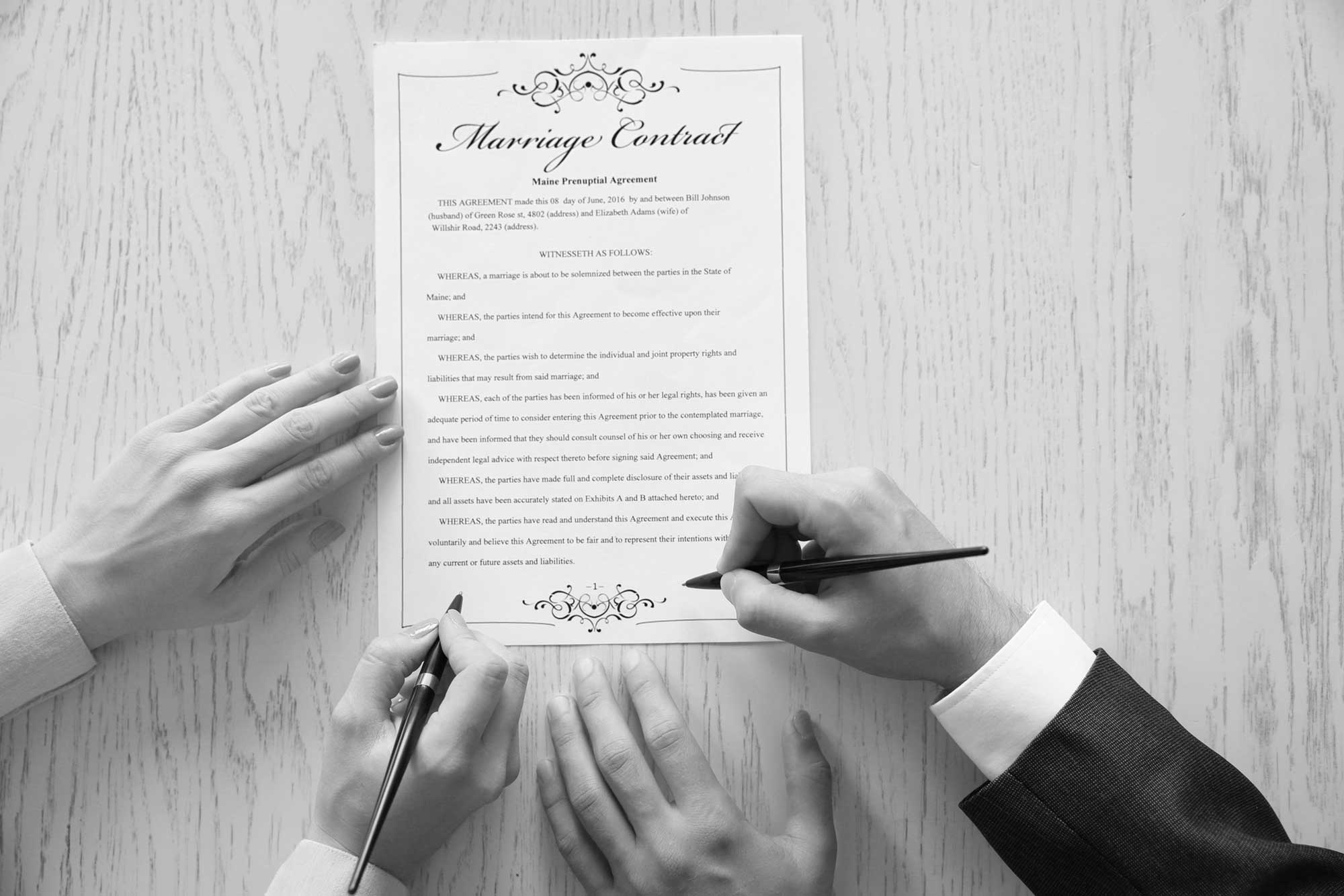 Image of two people signing a Prenup