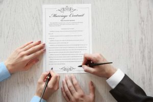 Stock photography image of a Marriage Contract on a table with the hands of a man and a woman signing it.