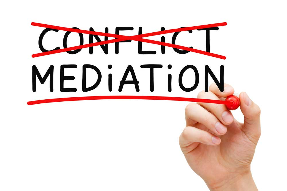 "Conflict Resolution image depicting the words ""conflict"" and ""mediation"" on a glass board. Person with red marker has crossed out ""conflict"" and is underling mediation."