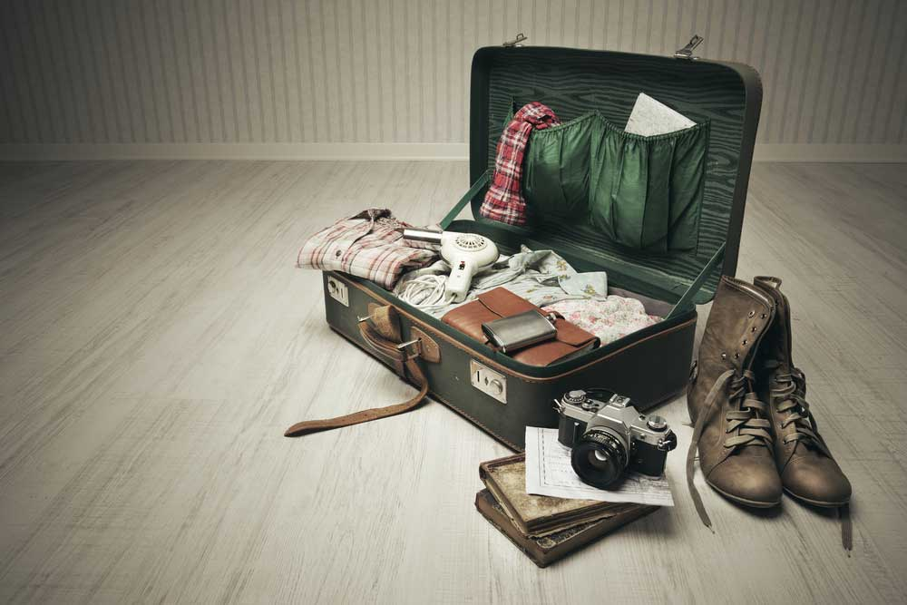 A vintage suitcase half neatly packed with necessities and important items in preparation for leaving.
