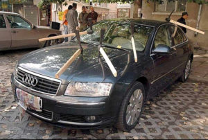 Image of an Audi sedan with six pick axes stuck into it depicting revenge in divorce. Ouch.